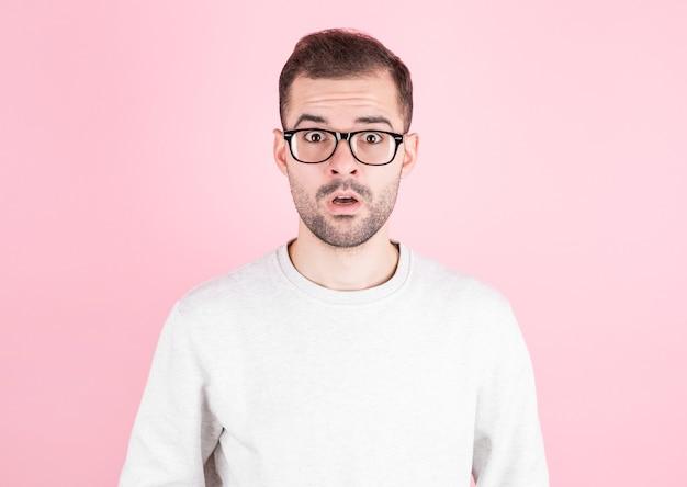 Überraschter mann in brille, die weißen pullover über rosa wand trägt