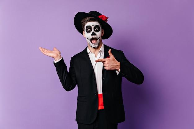 Überraschter mann in der formellen kleidung, die mit zombie-make-up aufwirft. kaukasischer typ, der sich auf halloween im mexikanischen stil vorbereitet.