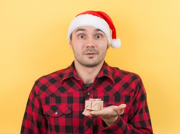 Überraschter mann in einem roten hut, der ein geschenk hält