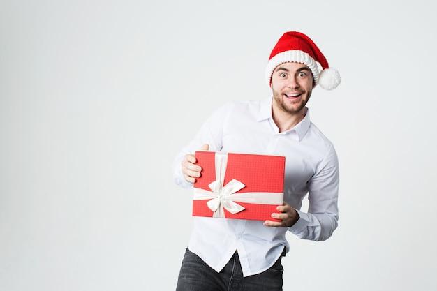 Überraschter mann in weihnachtsmütze mit geschenkbox