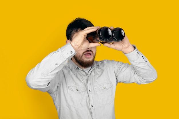 Überraschter mann mit bierflaschen in form eines fernglases über gelber wand