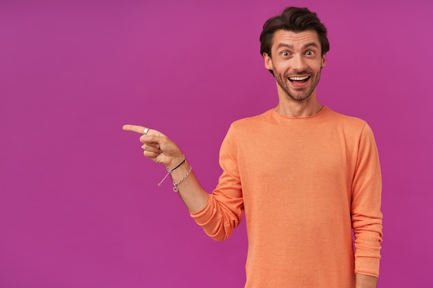 Überraschter mann mit brünetten haaren und borsten. trage einen orangefarbenen pullover. hat armbänder und ringe