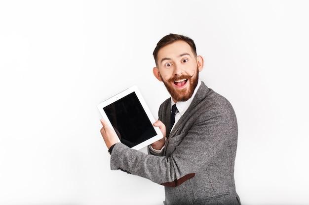 Überraschter mann mit rotem bart arbeitet mit tablette