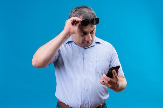 Überraschter mann mittleren alters im blau gestreiften hemd, das sonnenbrille hält handy auf blauem hintergrund hält