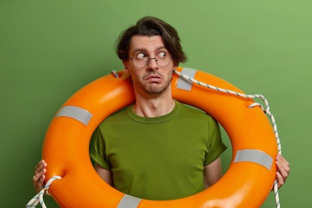 Überraschter mann posiert mit bojenring um den hals, schaut misstrauisch zur seite, lernt schwimmen, trägt transparente brille und grünes t-shirt, wird aus dem wasser gerettet,