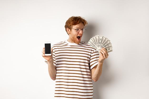 Überraschter rothaariger mann, der smartphone-app auf leerem bildschirm und geld zeigt, preisgeld online gewinnt und auf weißem hintergrund steht