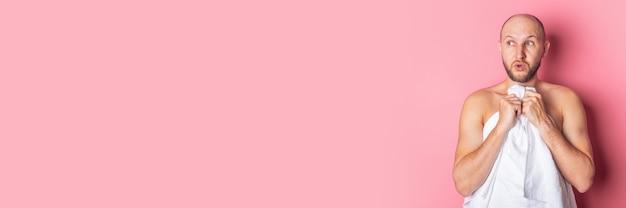 Überraschter schockierter junger mann smortit, um die nackte brust des handtuchs auf einer rosa oberfläche zu bedecken. banner.