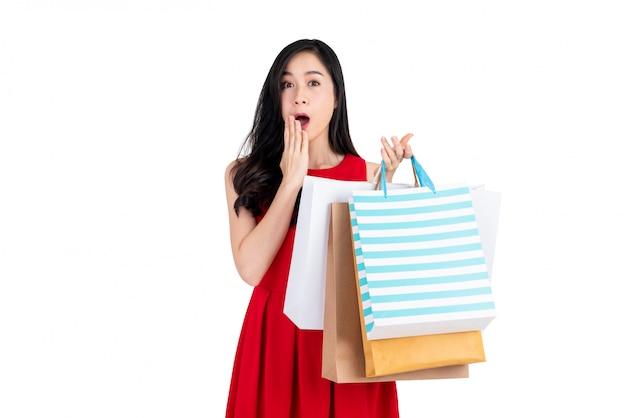 Überraschter schöner asiatischer käufer, der viele einkaufstaschen trägt