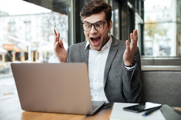 Überraschter schreiender geschäftsmann in den brillen, die durch die tabelle im café sitzen und laptop-computer schauen