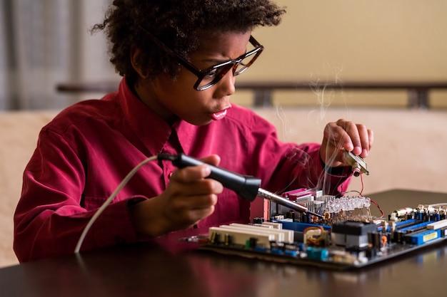 Überraschter schwarzer junge, der motherboard repariert