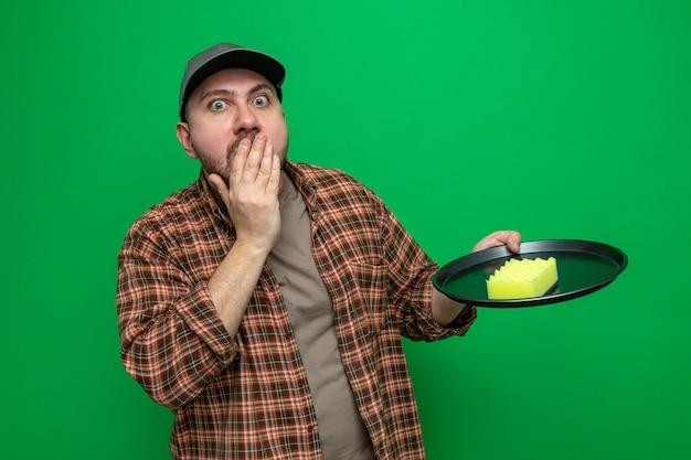 Überraschter slawischer putzmann, der sich die hand auf den mund legt und einen schwamm auf dem teller hält