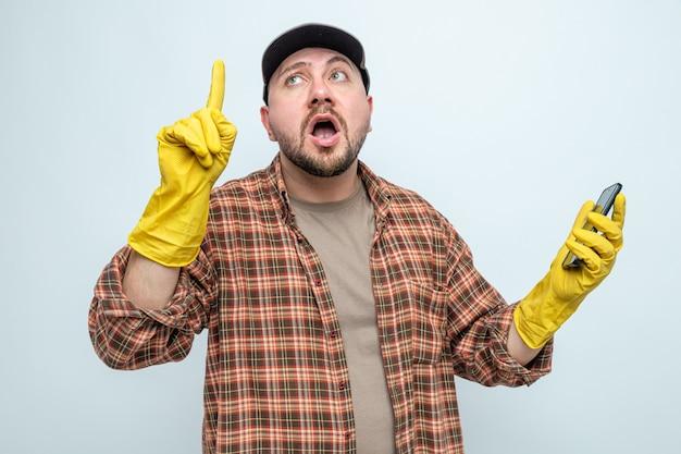 Überraschter slawischer putzmann mit gummihandschuhen, der das telefon hält und nach oben zeigt