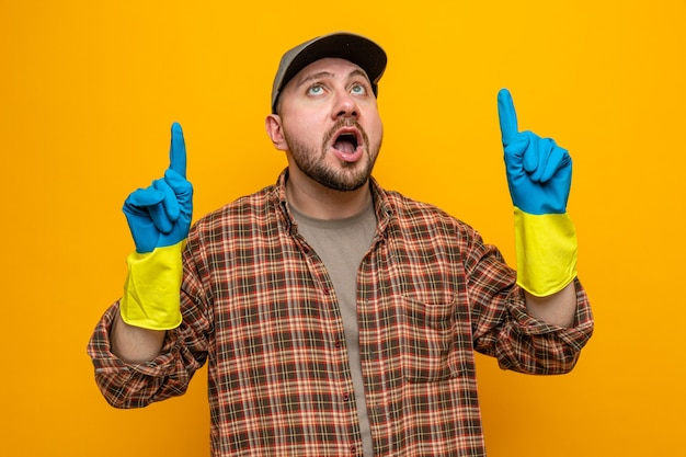Überraschter slawischer putzmann mit gummihandschuhen, der nach oben schaut und zeigt