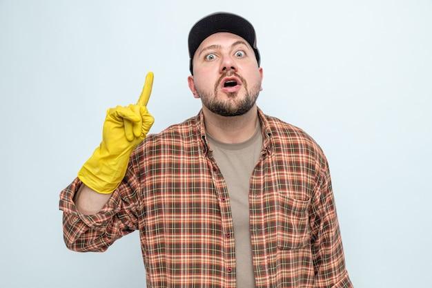 Überraschter slawischer putzmann mit nach oben zeigenden gummihandschuhen