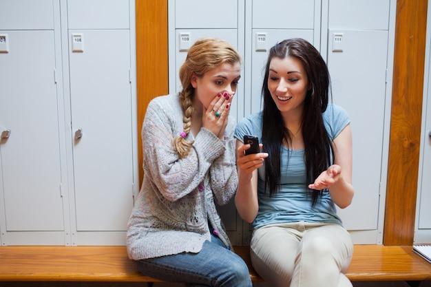 Überraschter student, der ihrem freund eine textnachricht zeigt