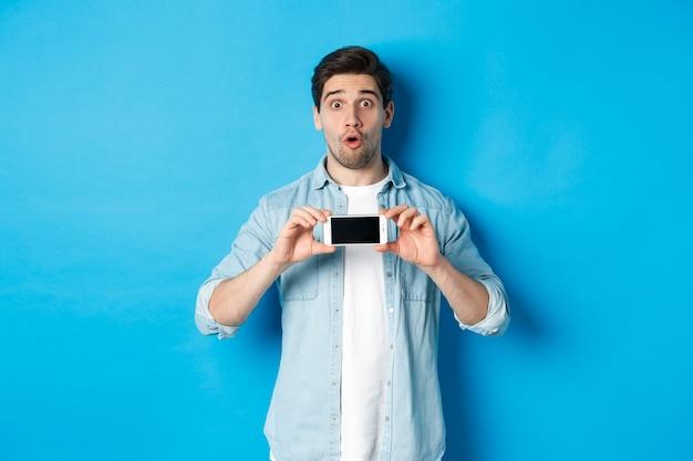 Überraschter typ, der handy-bildschirm zeigt und beeindruckt aussieht und auf blauem hintergrund steht