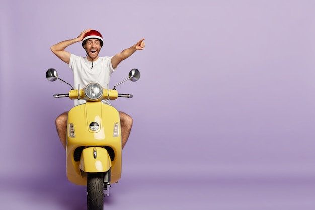 Überraschter typ mit helm fährt gelben roller