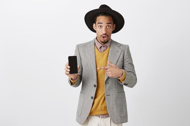 Überraschter und beeindruckter afroamerikaner, der über anwendung spricht und finger auf handybildschirm zeigt