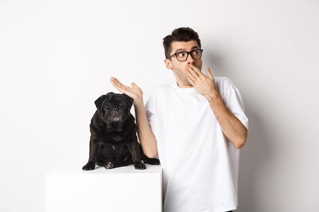 Überraschter und schockierter mann in brille, der in der nähe des niedlichen schwarzen hundes steht und direkt auf das logo starrt und über weiß posiert