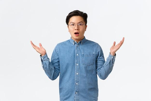 Überraschter und verwirrter asiatischer mann in klammern und brille kann nicht verstehen, wie das passiert ist, hebt die hände und zuckt erschrocken und verwirrt mit den schultern, weiß nicht, steht verblüfft auf weißem hintergrund.