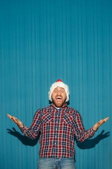 Überraschter weihnachtsmann, der eine weihnachtsmütze trägt