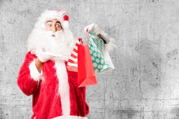Überraschter weihnachtsmann mit drei weihnachtsgeschenke