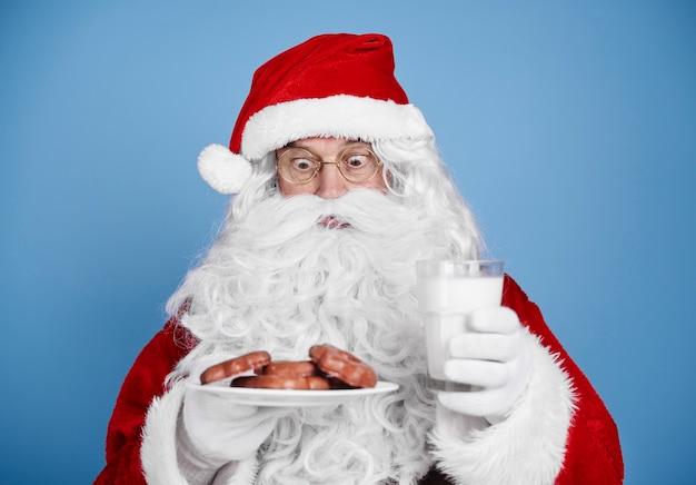 Überraschter weihnachtsmann mit milch und keks