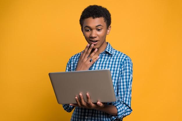 Überraschtes afroamerikanisches jugendlich betrachtet laptopschirm.