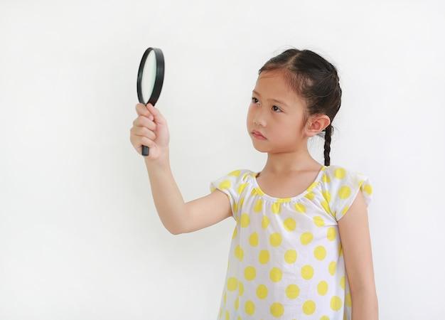 Überraschtes asiatisches kind, das durch eine lupe neben auf weißem hintergrund schaut