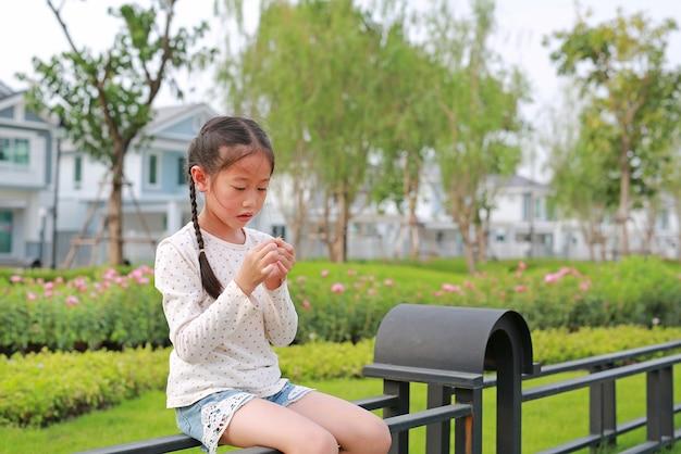 Überraschtes asiatisches kleines mädchen, das auf einem zaun sitzt und gras im garten im öffentlichen park hält
