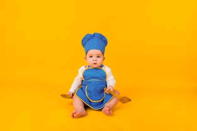 Überraschtes baby, das in einem kochkostüm auf einer gelben wand mit einem hölzernen spatel und einem löffel sitzt