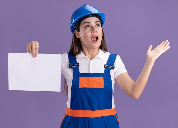 Überraschtes betrachten der jungen baumeisterfrau in uniform, die papierverbreitungshand lokalisiert auf purpurroter wand hält