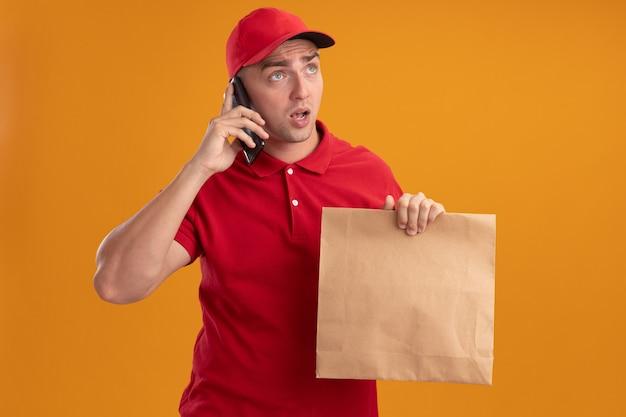 Überraschtes betrachten der seite junger zusteller, der uniform mit kappe hält, die papiernahrungsmittelpaket hält, spricht am telefon lokalisiert auf orange wand