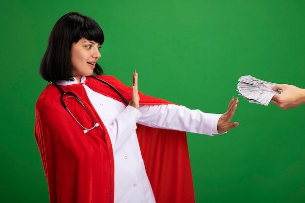 Überraschtes betrachten des jungen superheldenmädchens der seite, das stop-geste zeigt, die stethoskop mit medizinischem gewand trägt und jemanden umhüllt, der ihr geld gibt