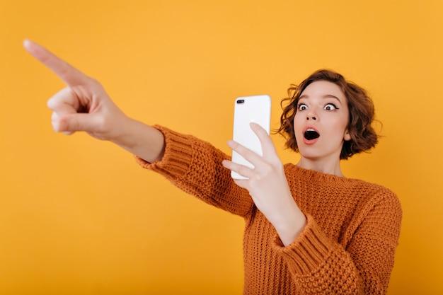 Überraschtes blasses mädchen mit überraschtem gesicht, das foto von jemandem macht