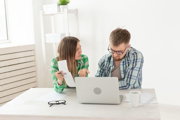 Überraschtes ehepaar. mann und frau denken über rechnungen für die bezahlung einer wohnung nach und sind schockiert über den betrag, den sie erhalten, indem sie die ergebnisse in ihrer haushaltsbuchhaltung auf einem laptop aufschreiben.