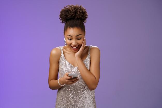 Überraschtes erstauntes junges afroamerikanisches mädchen, das smartphone-look-display hält, beeindruckte super glückliche lesenachrichten berühren wange weiten die augen und erhalten gerne großartige neuigkeiten, stehender blauer hintergrund.
