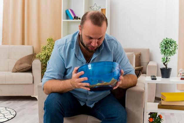 Überraschtes erwachsenes slawisches mann sitzt auf sessel, der schüssel des chips innerhalb des wohnzimmers hält und betrachtet