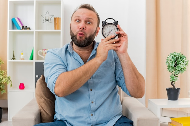 Überraschtes erwachsenes slawisches mann sitzt auf sessel, der wecker hält und kamera im wohnzimmer betrachtet