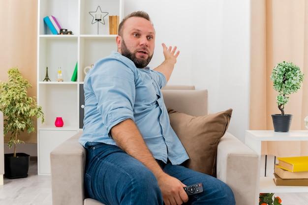 Überraschtes erwachsenes slawisches mann sitzt auf sessel, hält fernbedienung fern und zeigt hinter ins wohnzimmer