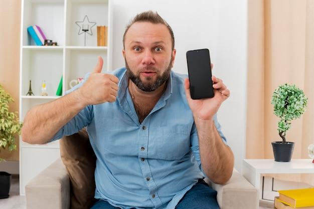 Überraschtes erwachsenes slawisches mann sitzt auf sessel und hält telefon und daumen hoch im wohnzimmer