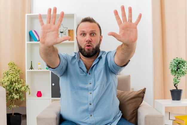 Überraschtes erwachsenes slawisches mann sitzt auf sessel und streckt zwei hände im wohnzimmer aus