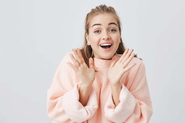 Überraschtes europäisches mädchen mit erhobenen händen erstaunt oder schockiert von unerwarteten nachrichten, die hände hochhalten und glücklichen ausdruck zeigen. junge blonde frau, die posotove emotionen zeigt.