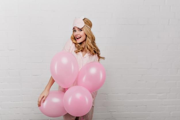 Überraschtes fröhliches mädchen in der schlafmaske, die auf weißer wand mit partyballons steht. porträt der schönen jungen dame, die etwas am wochenendmorgen feiert.