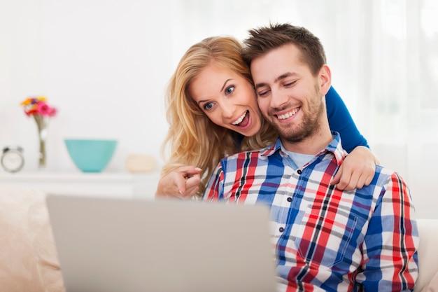Überraschtes glückliches paar, das laptop betrachtet