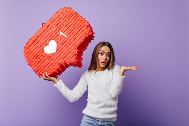 Überraschtes gut gekleidetes mädchen, das mit rotem banner aufwirft. innenporträt der emotionalen bloggerin im flauschigen pullover.