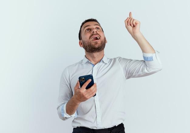 Überraschtes gutaussehendes mann hält telefon, das lokal auf weiße wand schaut und zeigt