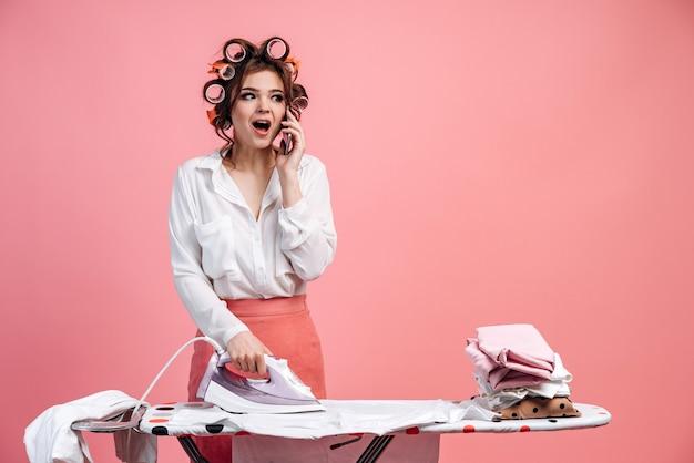 Überraschtes hausfrauenmädchen mit lockenwicklern auf dem kopf bügelt einen berg von kleidern am telefon und ist aus irgendeinem grund sehr überrascht hübsche hausfrau macht sich sorgen um die hausarbeit