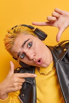 Überraschtes hipster-mädchen sucht perfekte perspektive macht handrahmen misst winkel hat erstaunten ausdruck lebendiges make-up gelbes haar hört lieblingsmusik macht ein bild von momentposen im innenbereich