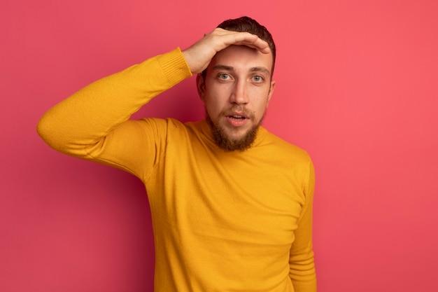 Überraschtes hübsches blondes mann hält handfläche an der stirn auf rosa